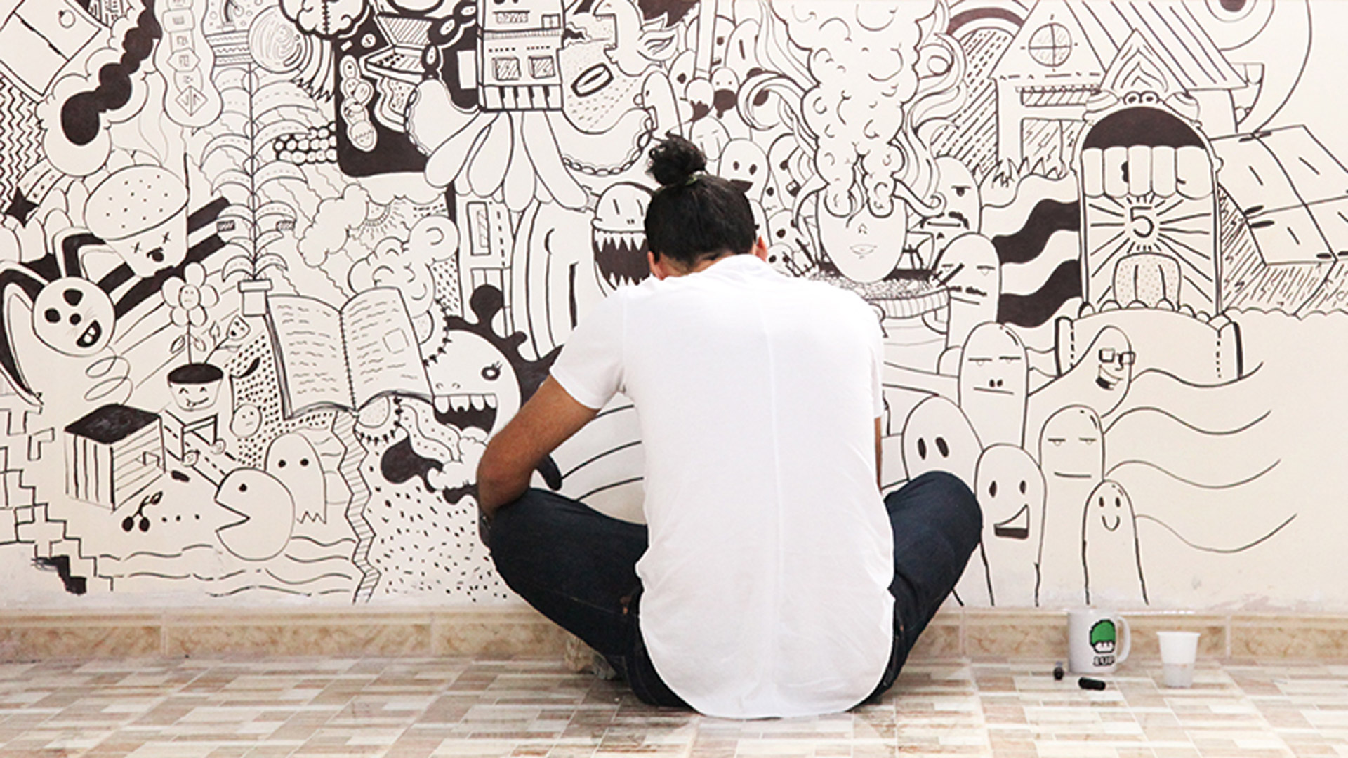 Designer Khaled Bader drawing a mural in the new Tanarout centre.